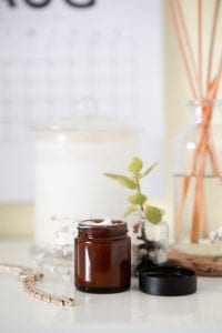 Green leafed plant, brown glass jar, and items on white surface; image by Maddi Bazzocco, via Unsplash.com.