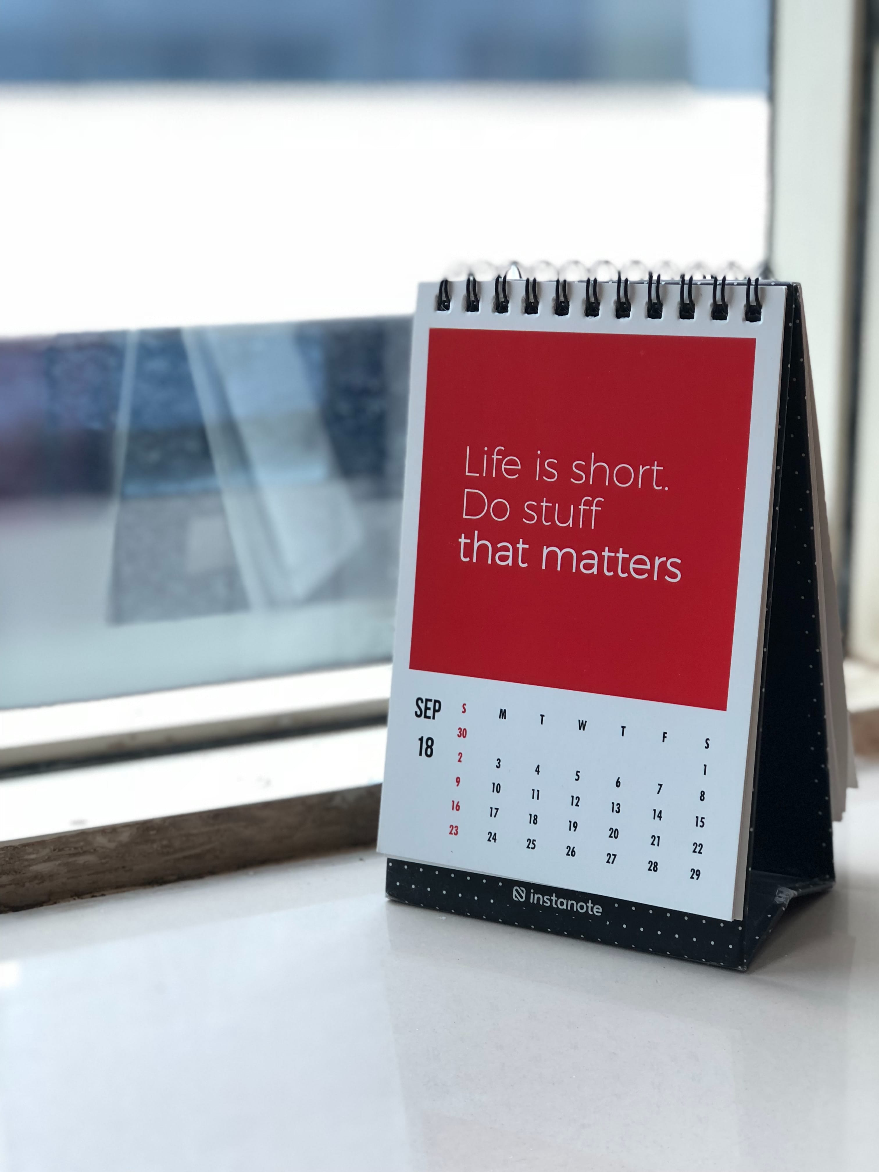 "Spiral freestanding calendar on white surface. Print says ""Life is short. Do stuff that matters."" Image by Manasvita S, via Unsplash.com."