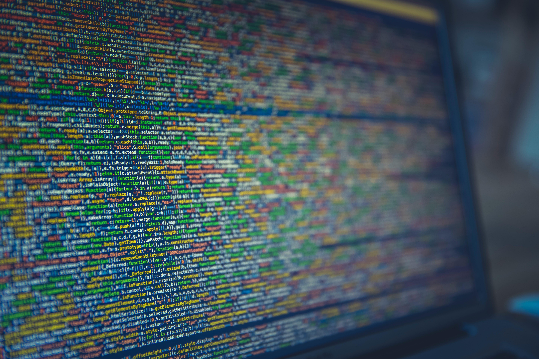 Long colorful lines of code on a computer screen; image by Markus Spiske, via Unsplash.com.