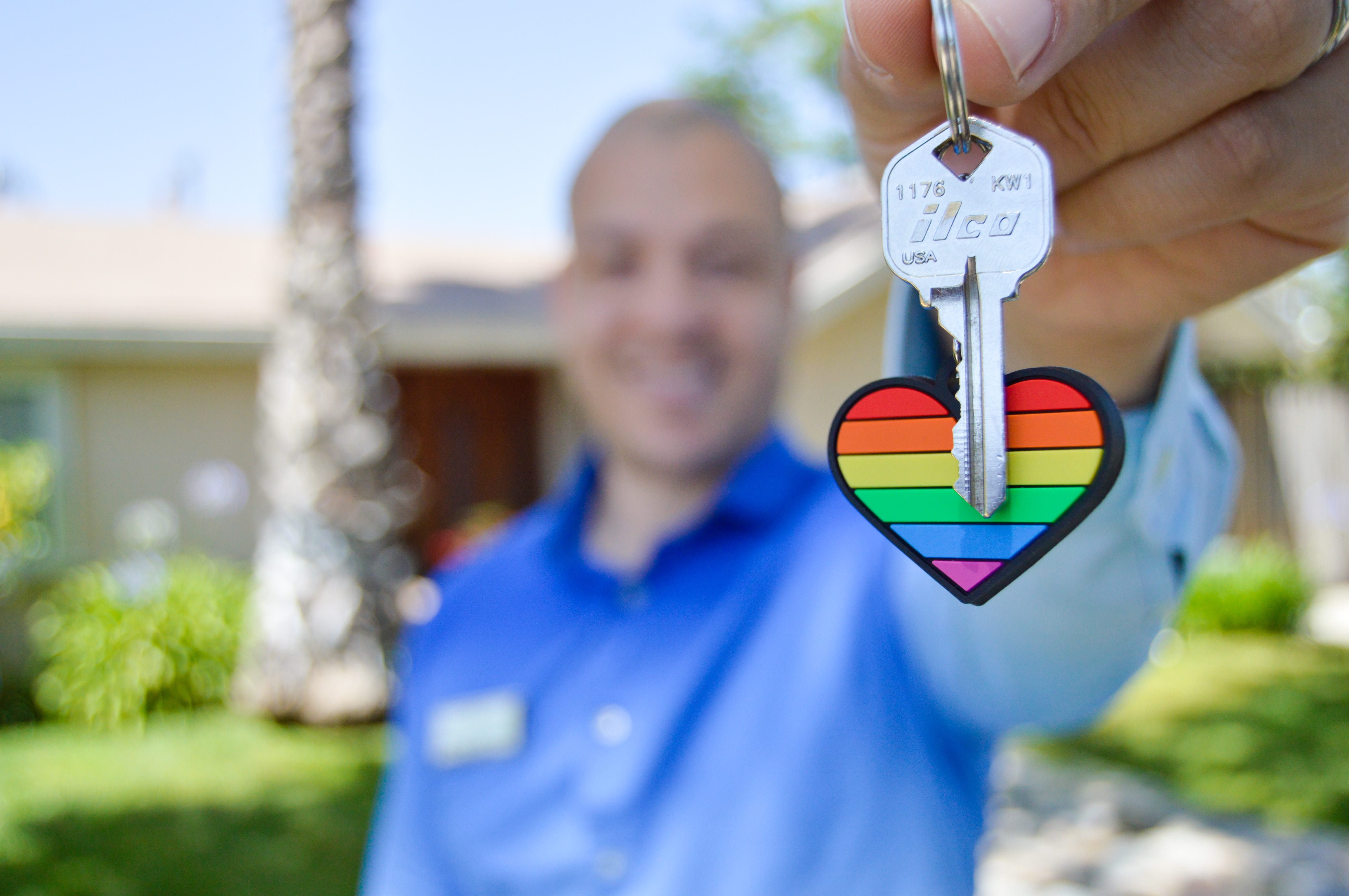 Man in blue shirt holding out key on heart shaped, rainbow keyring; image by Maurice Williams, via Unsplash.com.