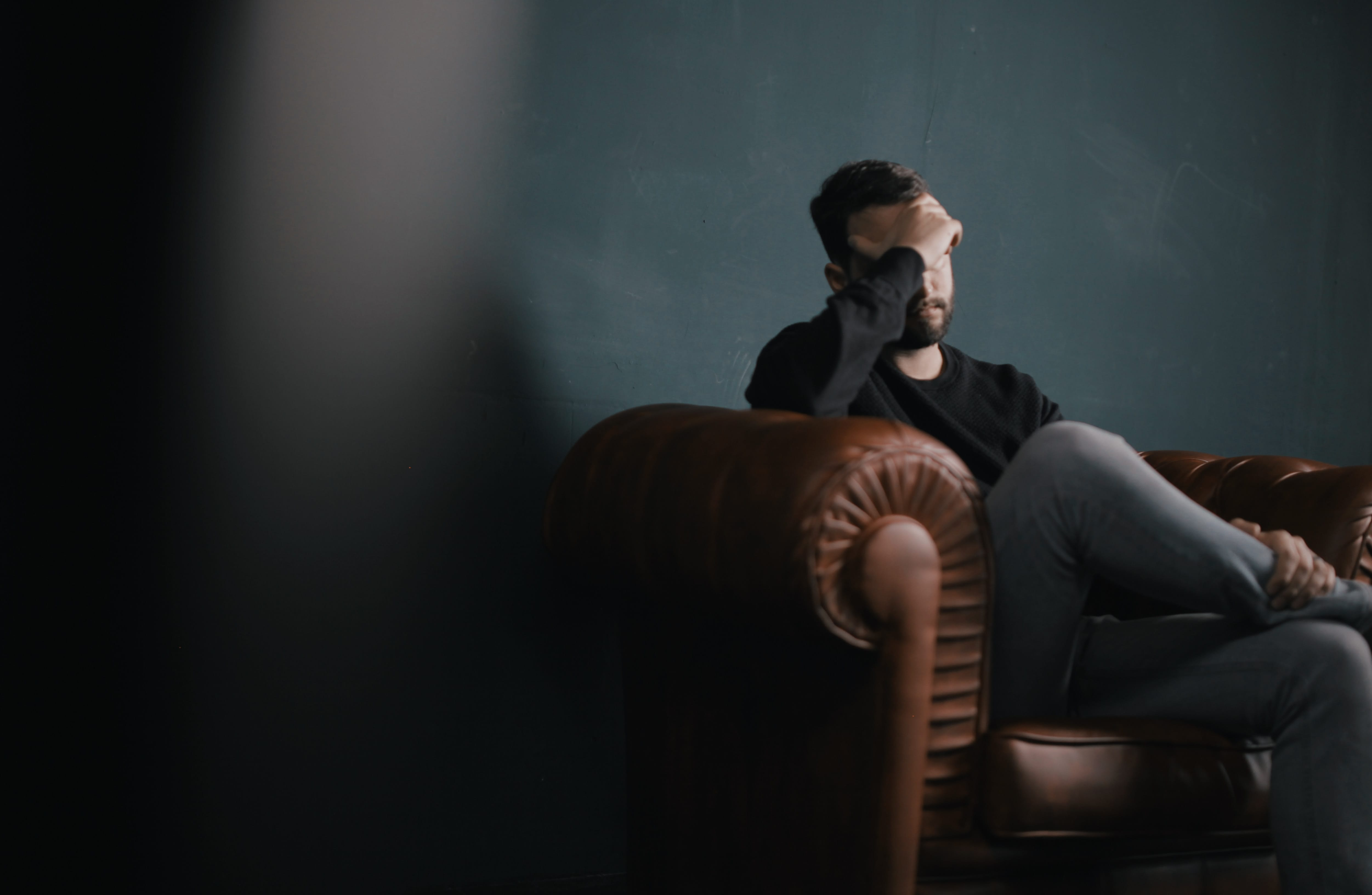 Man sitting on sofa resting his head in his hand; image by Nik Shuliahin, via Unsplash.com.
