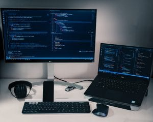 Computer monitor, keyboard, mouse and laptop on a desk; image by Pakata Goh, via Unsplash.com.