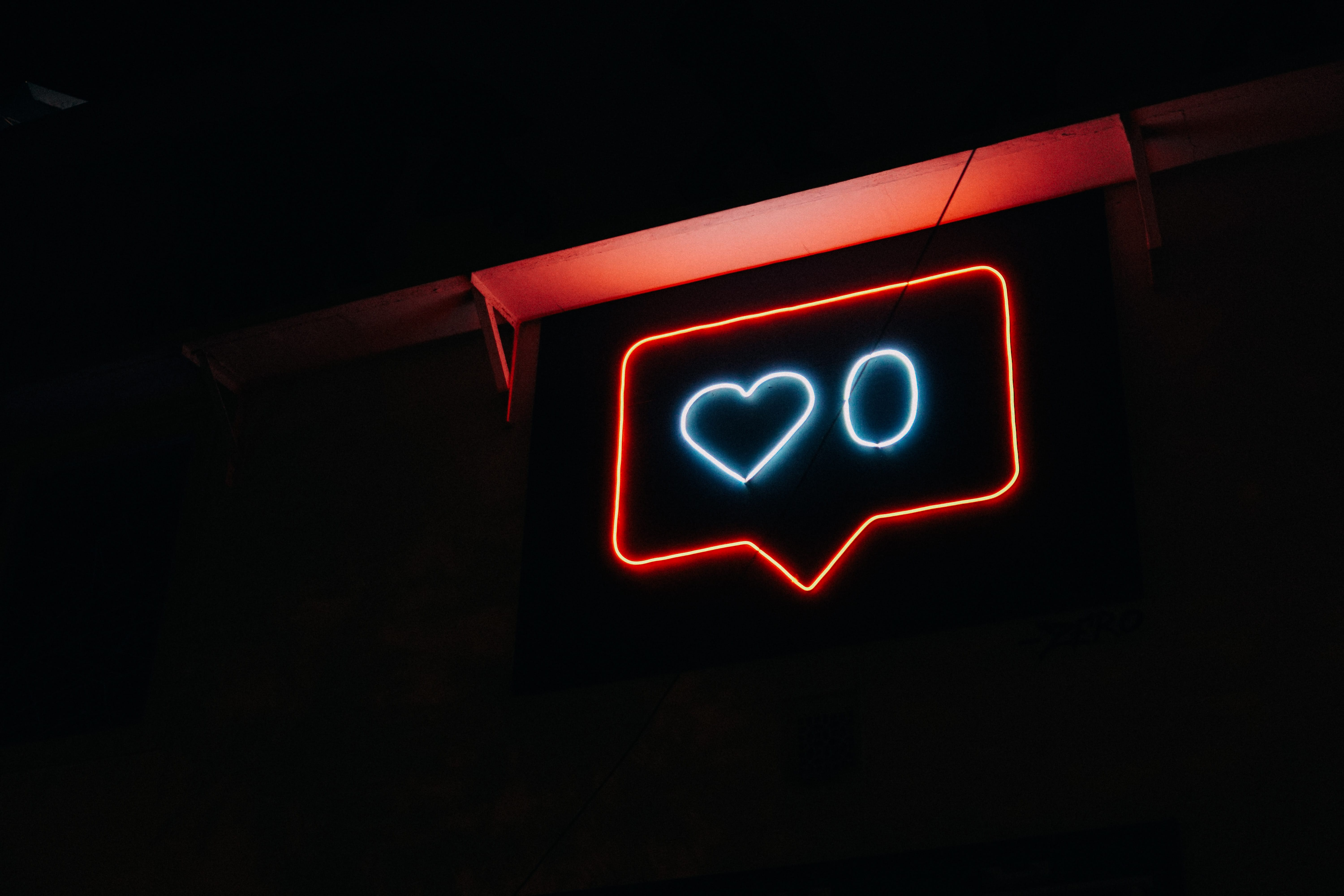 Red and blue neon sign showing a comment bubble and zero likes against a black background; image by Prateek Katyal, via Unsplash.com.