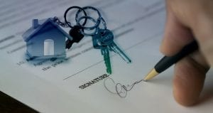 Keyring with small house on it sitting on top of purchase contract as man signs it; image by geralt, via Pixabay, no changes made.
