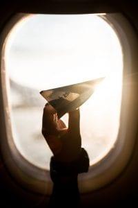 Child holding paper airplane in front of an airplane window; image by Sebastián León Prado, via Unsplash.com.
