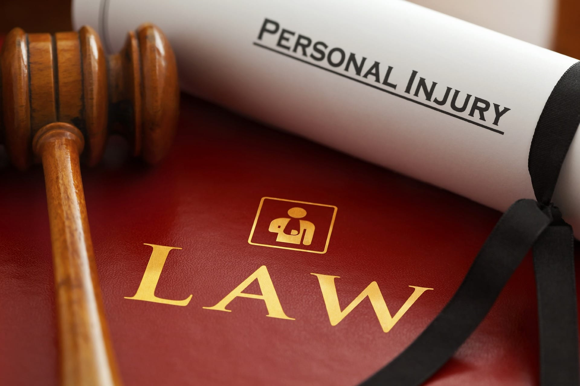 "Gavel and rolled paper with ""Personal Injury"" on it sitting on top of dark red binder titled ""Law."" Image by Claimaccident, via pixabay.com. No changes."