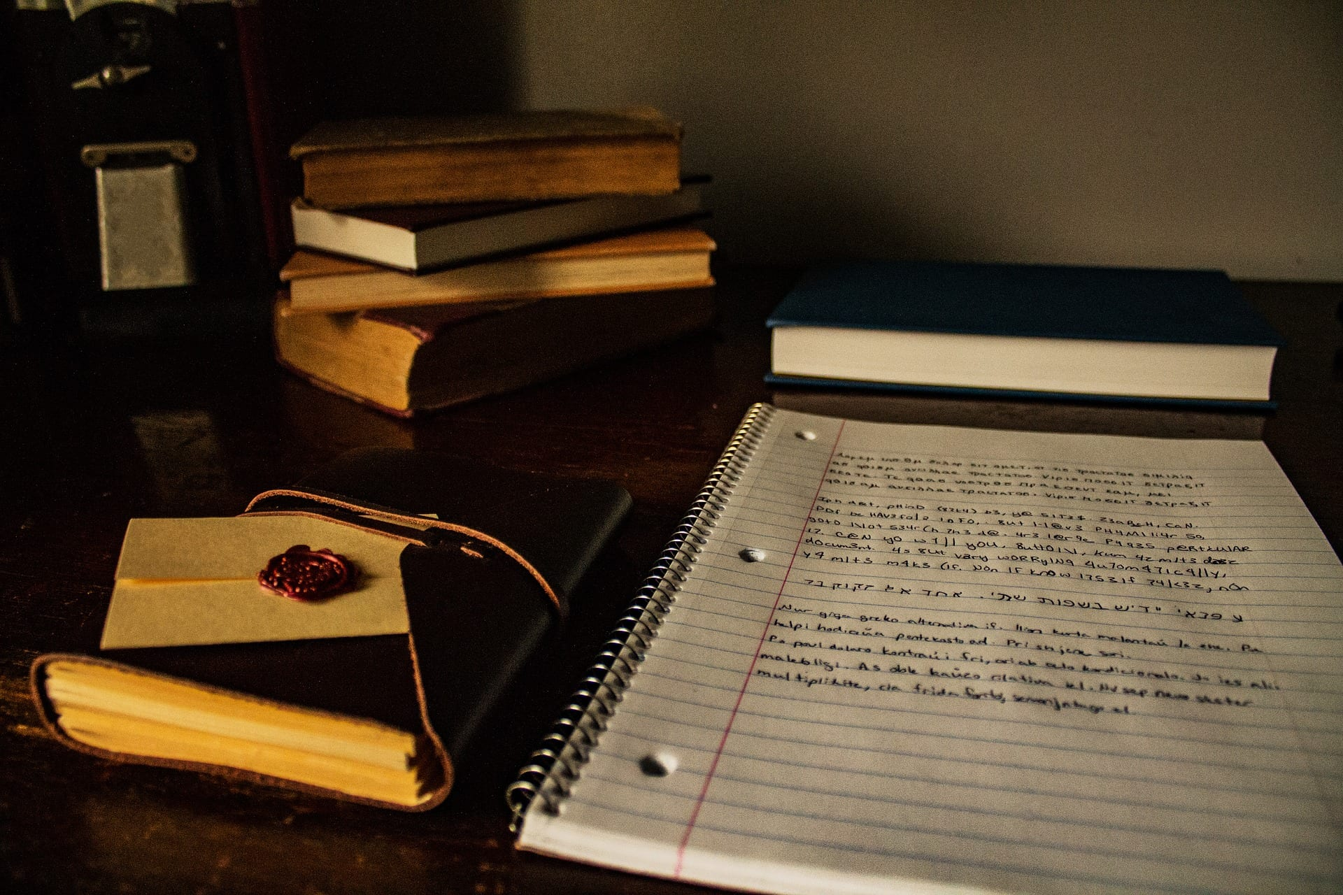 Books and a spiral-bound notebook of notes on a desk; image by Chloestrong, via Pixabay.com.