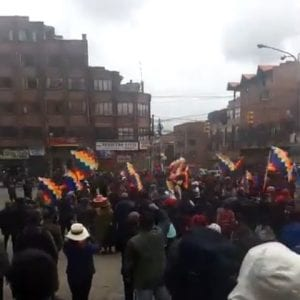 A gathering of people on a city street holding aloft colorful flags.