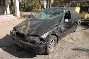 Black sedan with serious front-end damage; image by Byrev, via Pixabay.com.