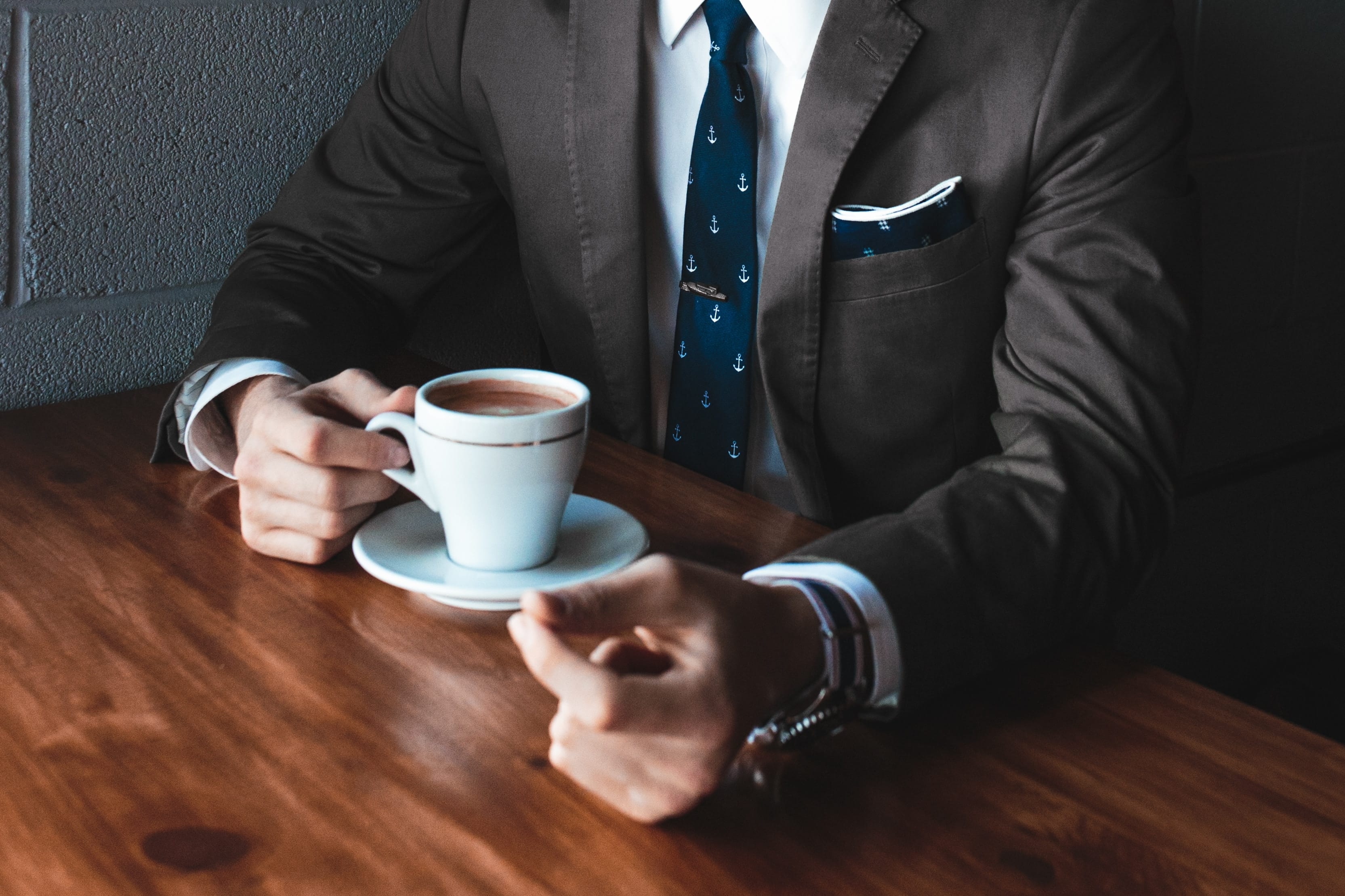 Man holding cup filled with coffee on table; image by Andrew Neel, via Unsplash.com.