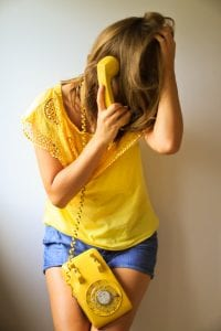 Woman in blue shorts and yellow top using a yellow rotary phone, her hand in her hair; image by Eva Sol, via Unsplash.com.