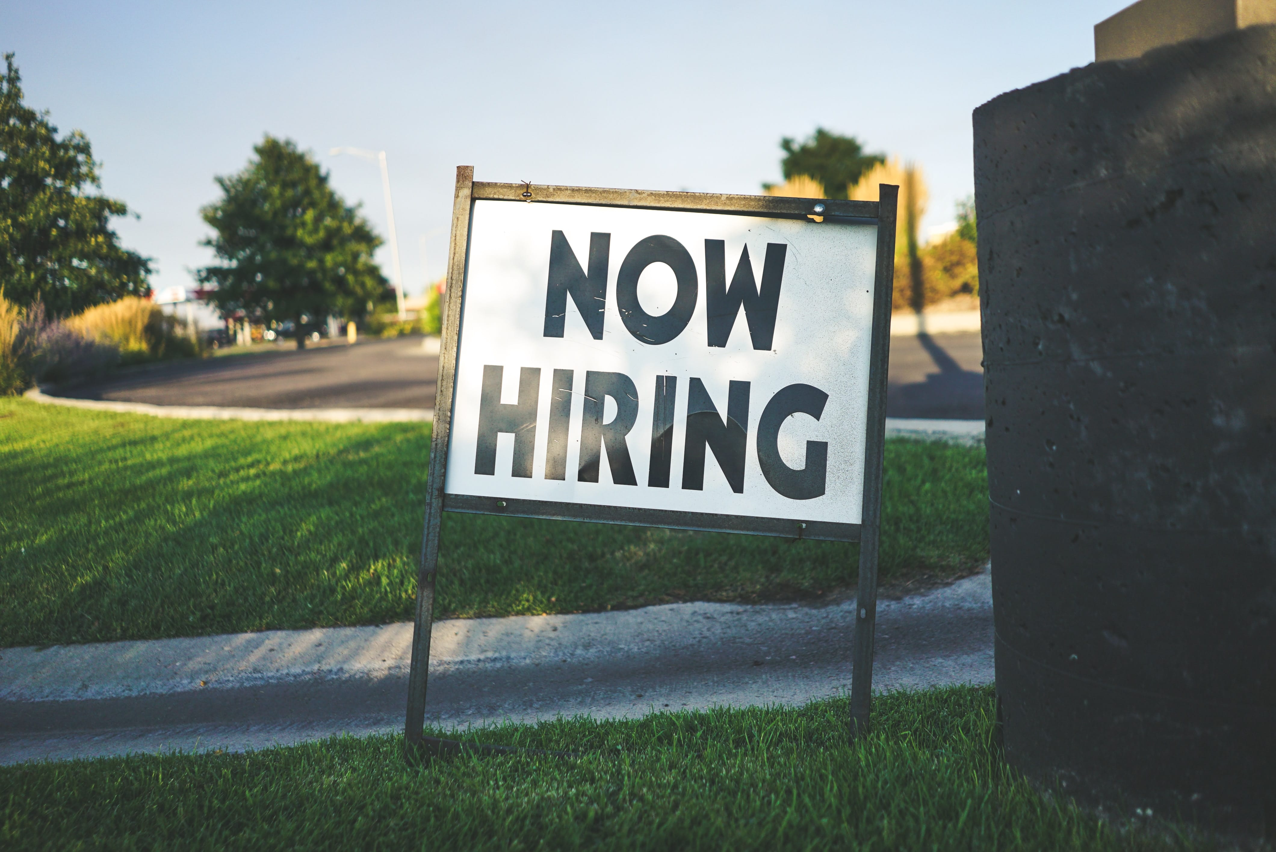Now Hiring sign on lawn; image by Free To Use Sounds, via Unsplash.com.