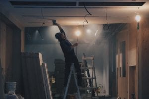 Man on ladder, working on ceiling in construction; image by Henry & Co., via Unsplash.com.