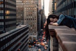 Woman leaning on top building rail during daytime; image by Hernan Sanchez, via Unsplash.com.