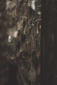 Silver-colored dog tags hanging on hooks shallow focus photography; image by Holly Mindrup, via Unsplash.com.