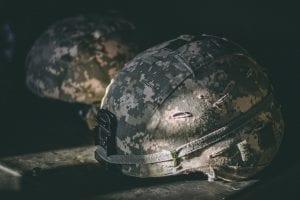 Gray and brown camouflage nutshell helmet on table; image by Israel Palacio, via Unsplash.com.