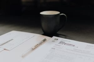 Desk with tax papers, pen, and coffee mug; image by Kelly Sikkema, via Unsplash.com.
