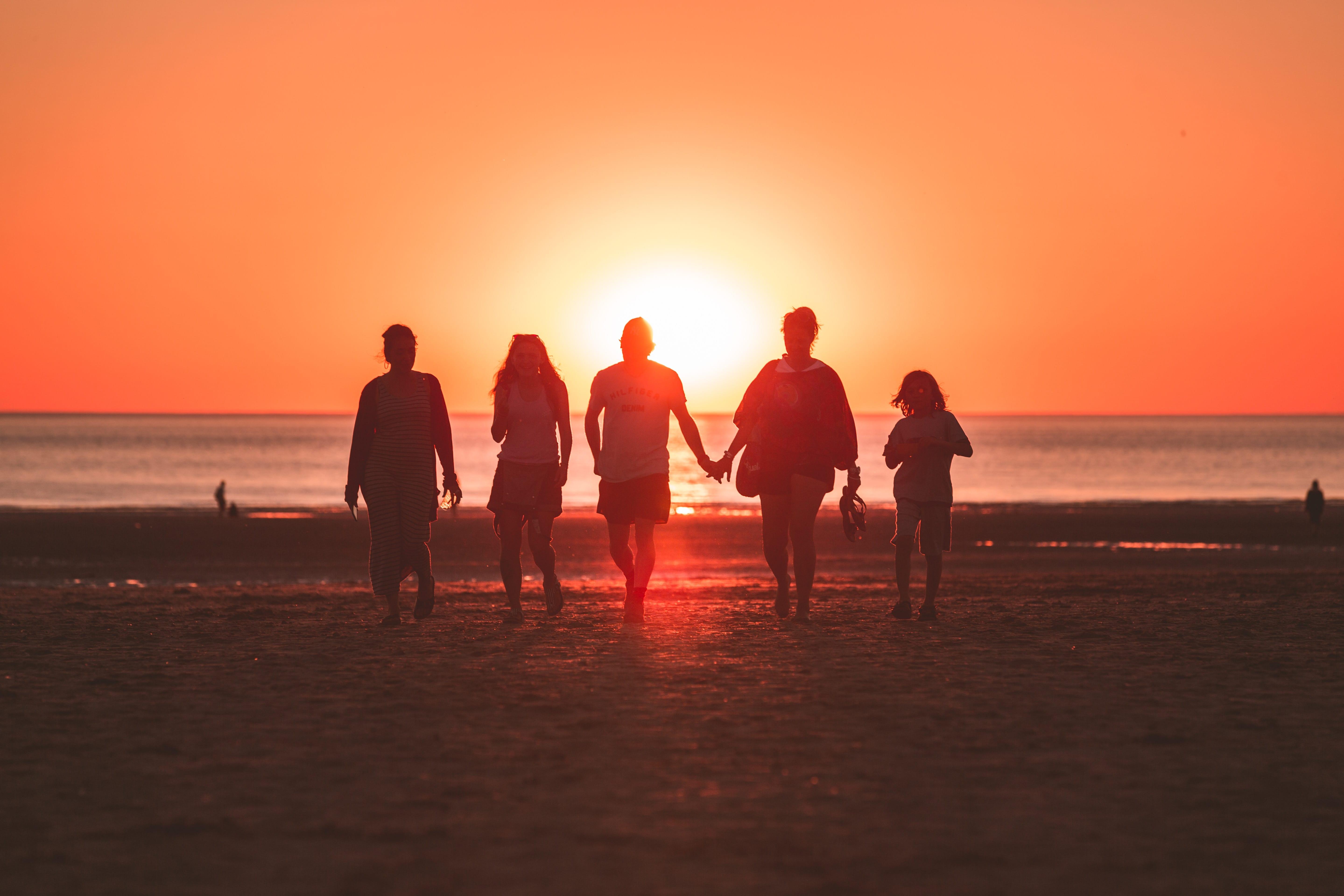 Family of five walking along beach at sunset; image by Kevin Delvecchio, via Unsplash.com.