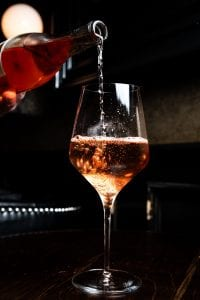 Person pouring pink wine into wine glass; image by Kevin Kelly, via Unsplash.com.
