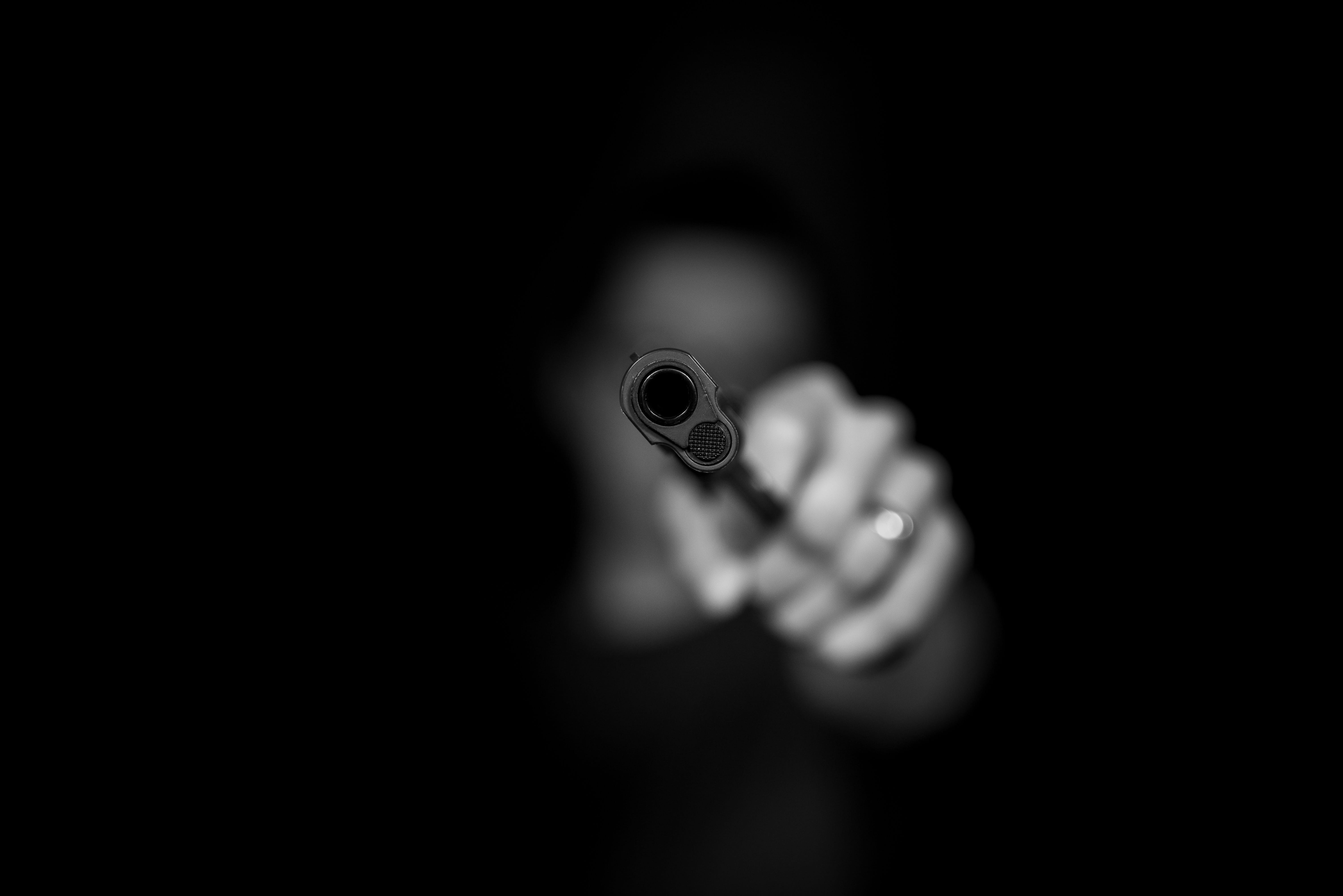 Greyscale image of person pointing a gun at viewer; image by Max Kleinen, via Unsplash.com.