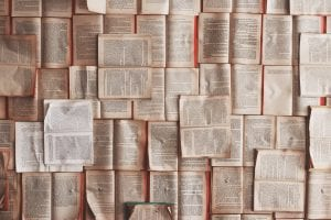 Open books, arranged end-to-end; image by Patrick Tomasso, via Unsplash.com.