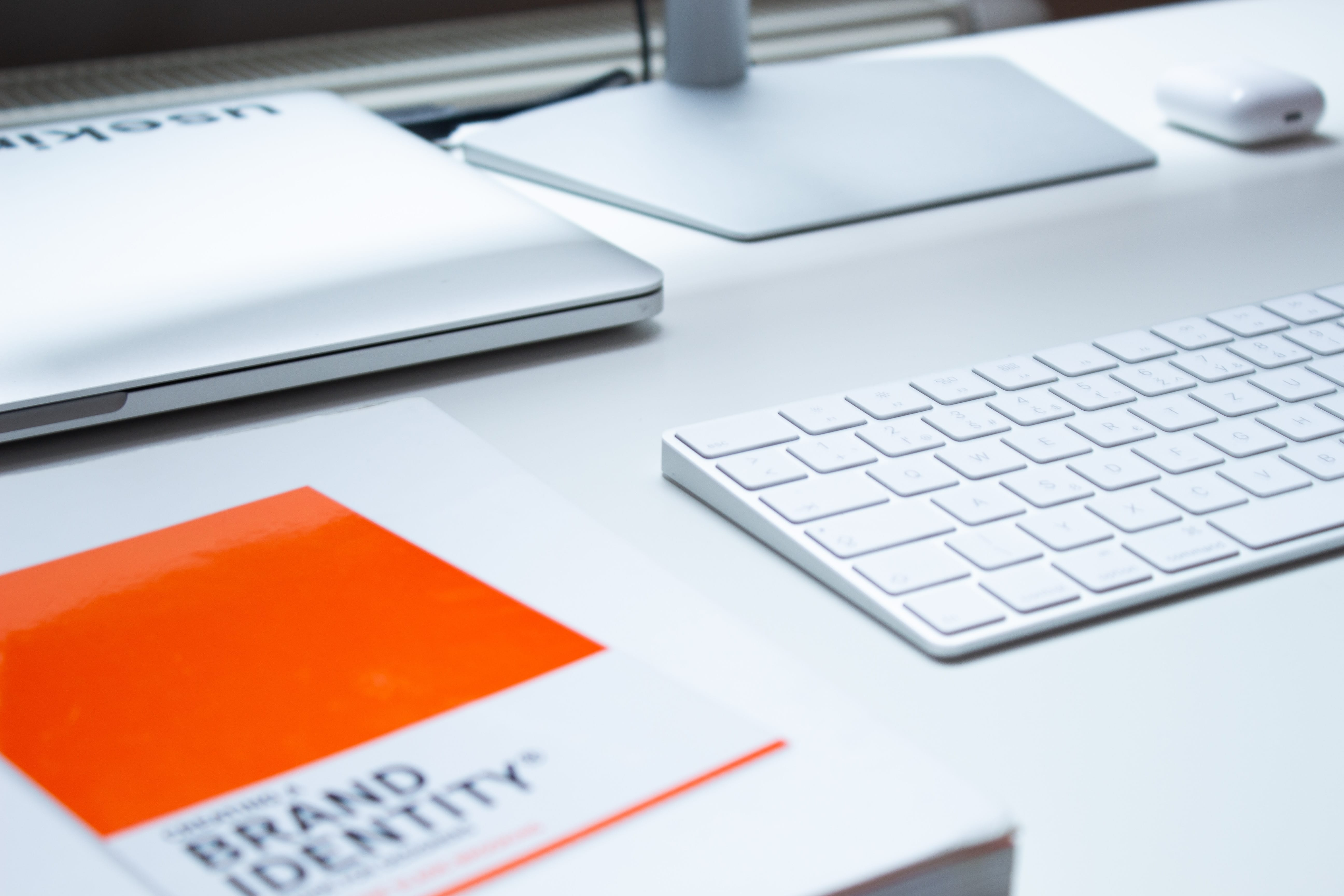 "White desk with white laptop and keyboard and orange & white book titled ""Brand Identity."" Image by Patrik Michalick, via Unsplash.com."