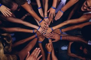 Team doing a hands-in huddle; image by Perry Grone, via Unsplash.com.