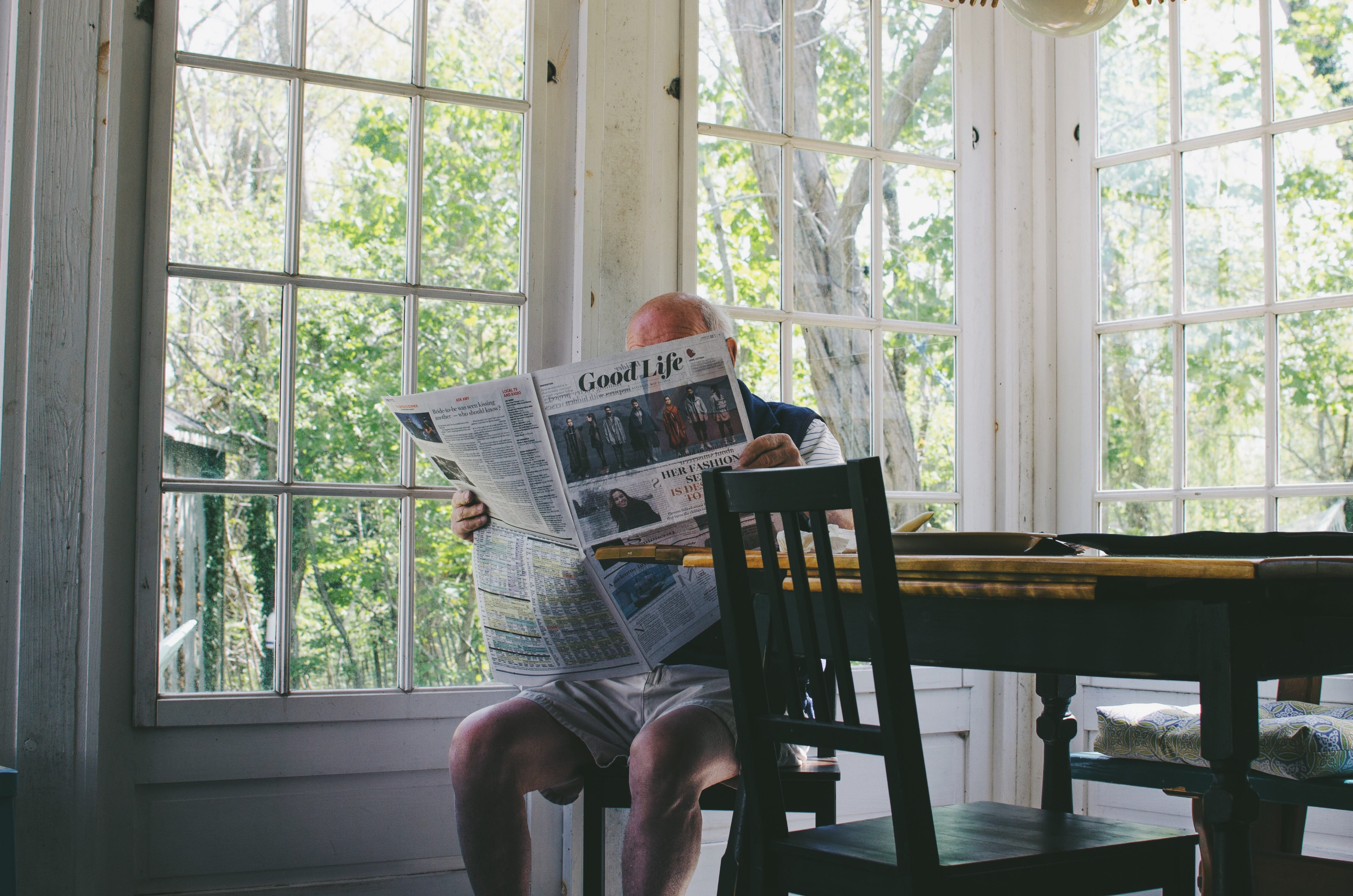 Man sitting at table reading newspaper; image by Sam Wheeler, via Unsplash.com.