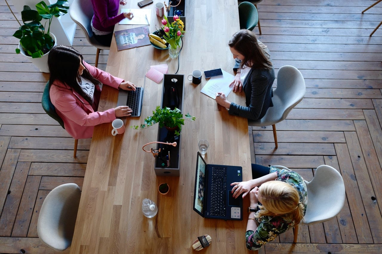 Three women sitting at common table using laptops; image by CoWomen, via Pexels.com.