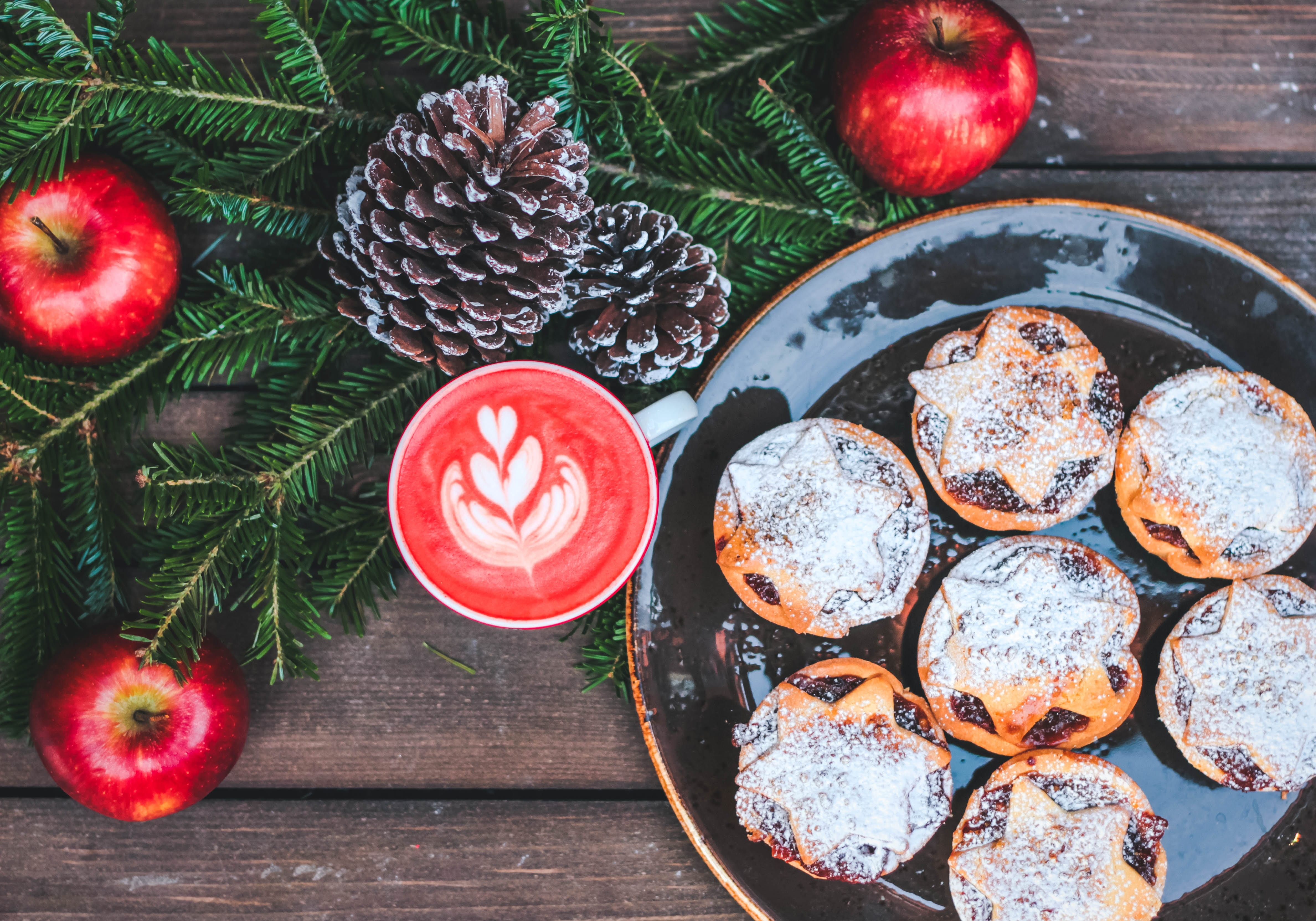 Pastries on black ceramic plate, red velvet cappuccino, red apples and pine cones on table; image by Toa Heftiba, via Unsplash.com.