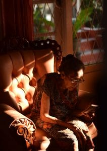 Woman reading in armchair; image by Yoshua Giri, via Unsplash.com.