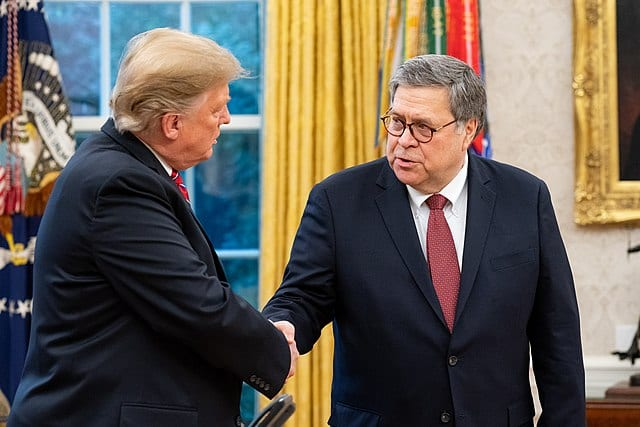 Two aging white men in suits, shaking hands.