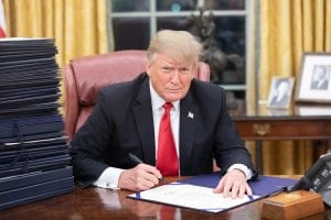 President Trump signing a stack of papers in the Oval Office.