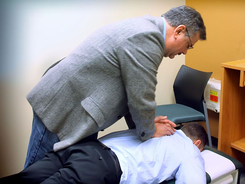 A chiropractor performs an adjustment on a patient