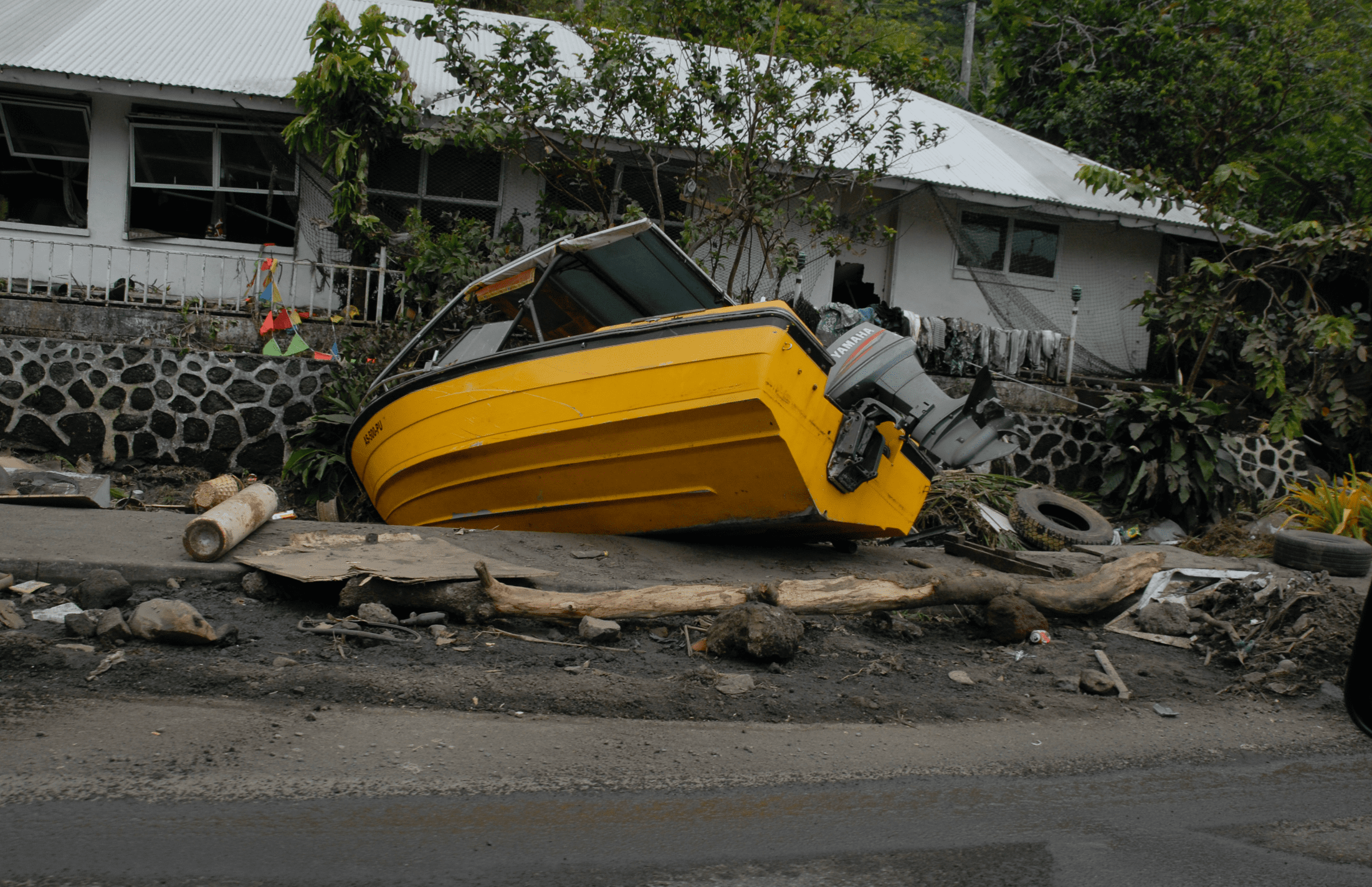 Boat pushed into front yard of home in American Samoa by tsunami in 2009; image by Casey Deshong of FEMA, public domain.