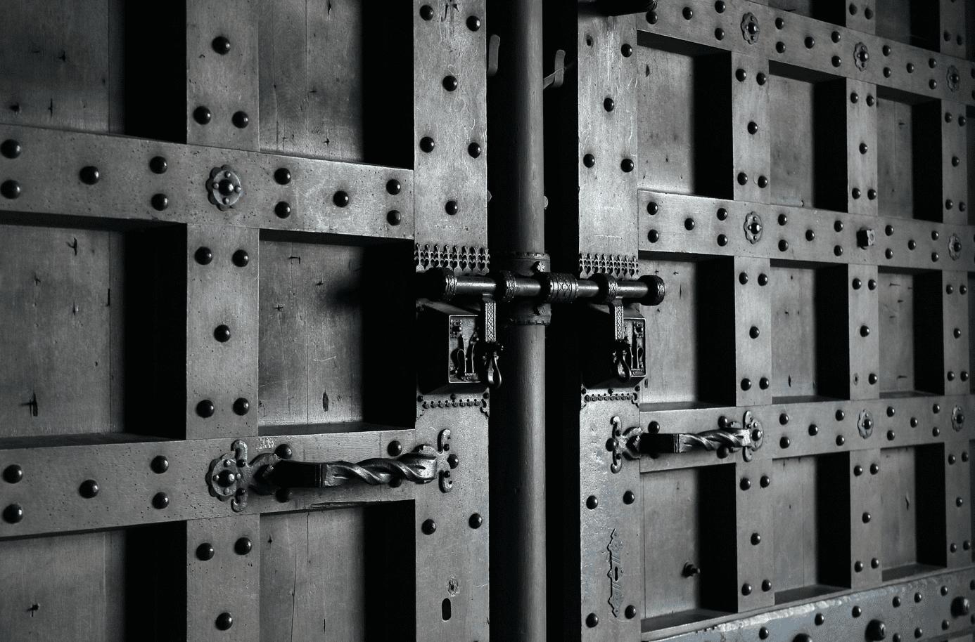 Locked metal door; image by Broesis, via Pixabay.com.