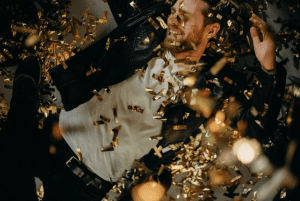 Man in black leather jacket dancing in confetti; image by CottonBro, via Pexels.com.