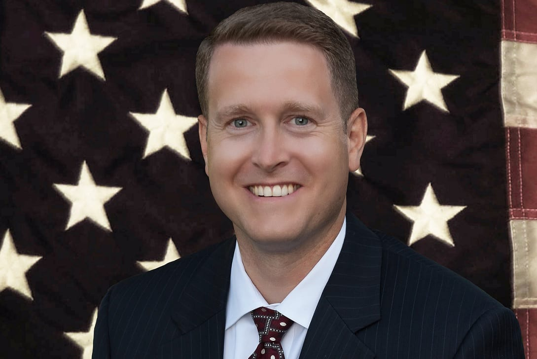 A Caucasian man with short brown hair, wearing a dark suit, standing in front of a large American flag.