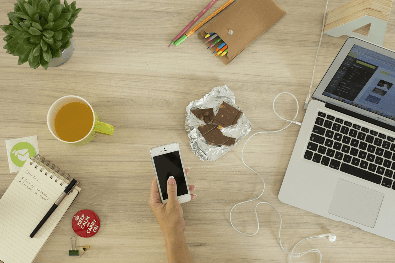 Man at desk with smartphone, laptop, tea, chocolate and a plant; image by Chris Adamus, via Unsplash.com.