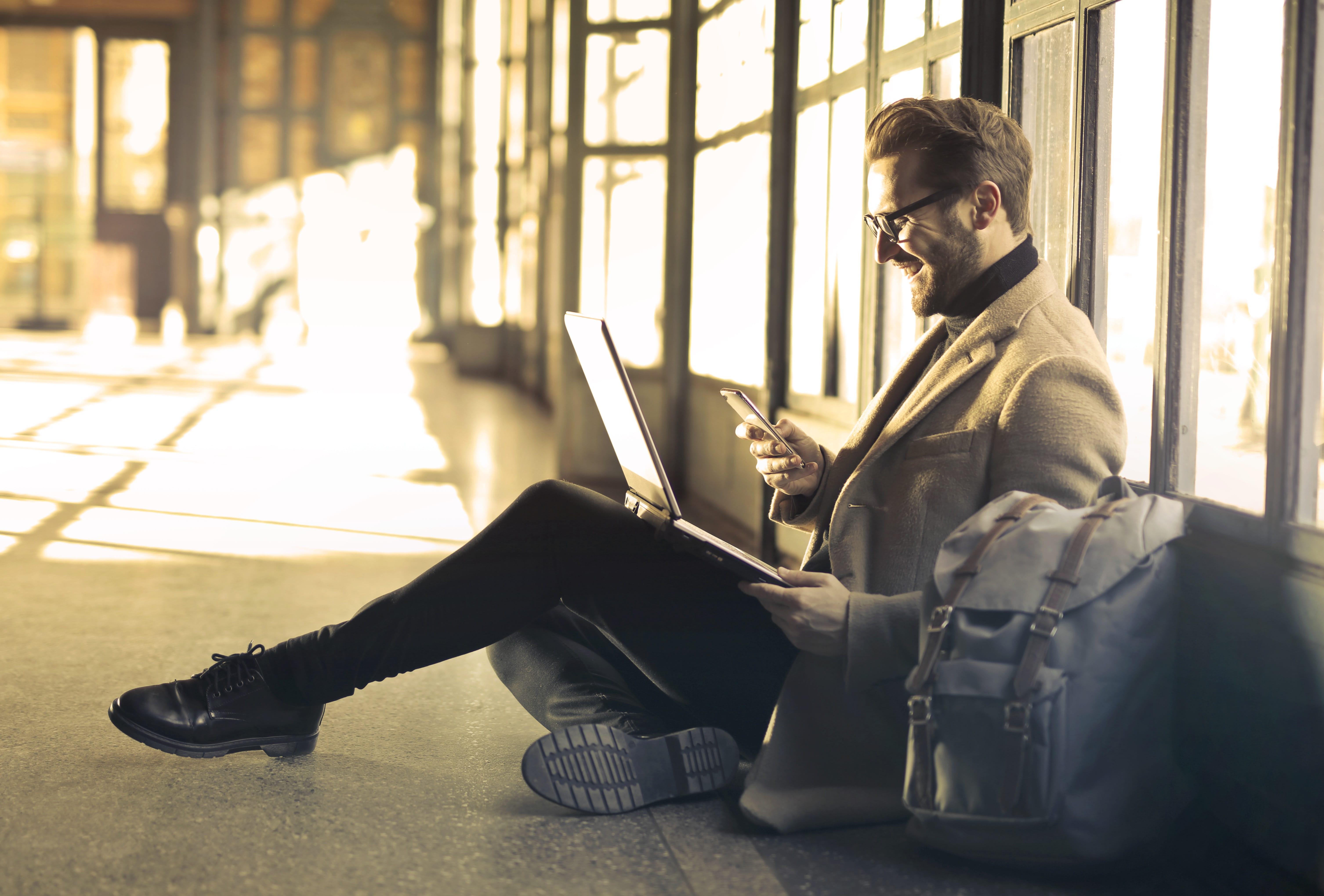 Man sitting near window holding phone and laptop; image by Bruce Mars, via Unsplash.com.