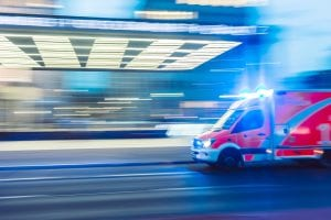 Red ambulance in time-lapse photography; image by Camilo Jiminez, via Unsplash.com.