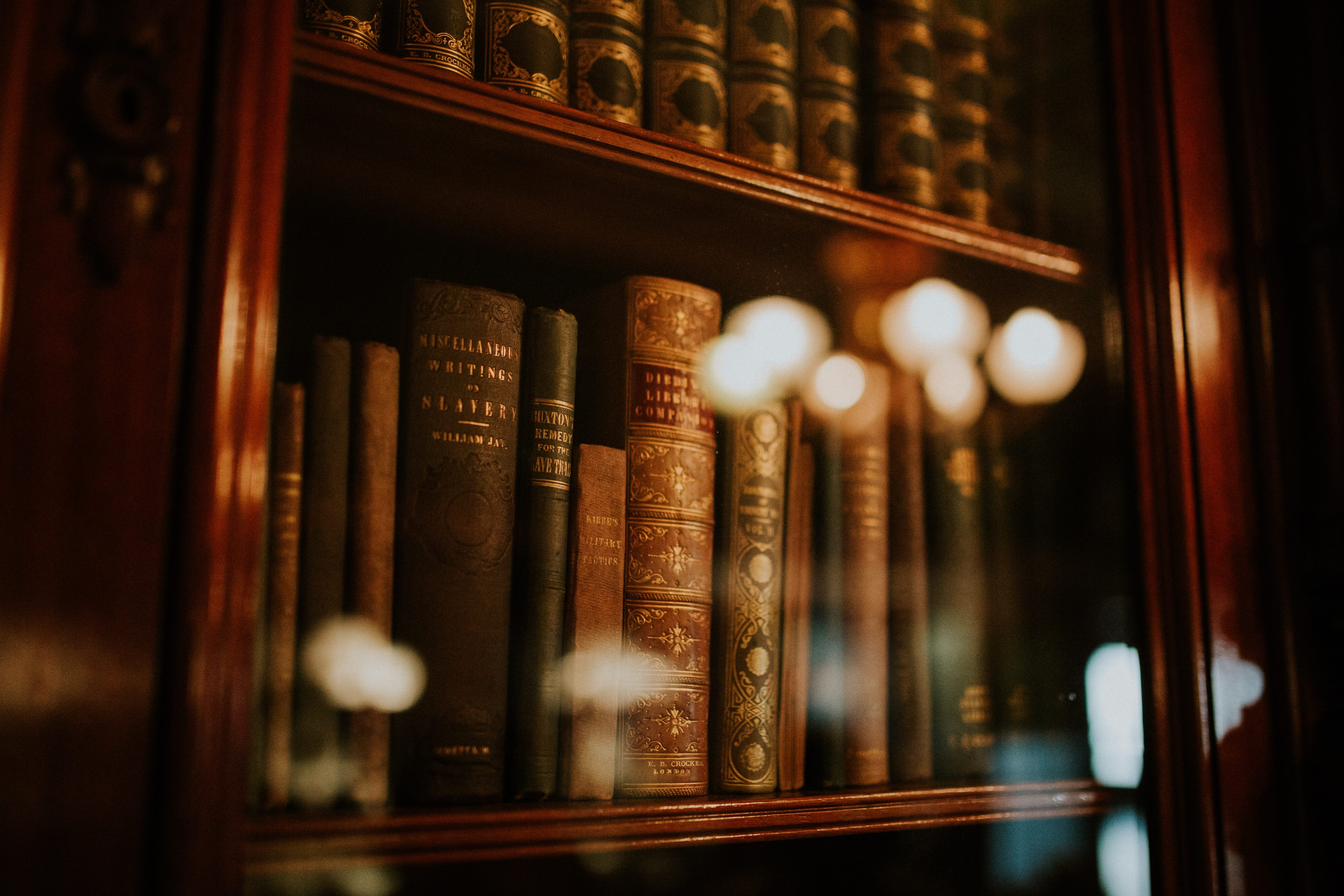 Books in bookcase with glass door; image by Clarisse Meyer, via Unsplash.com.