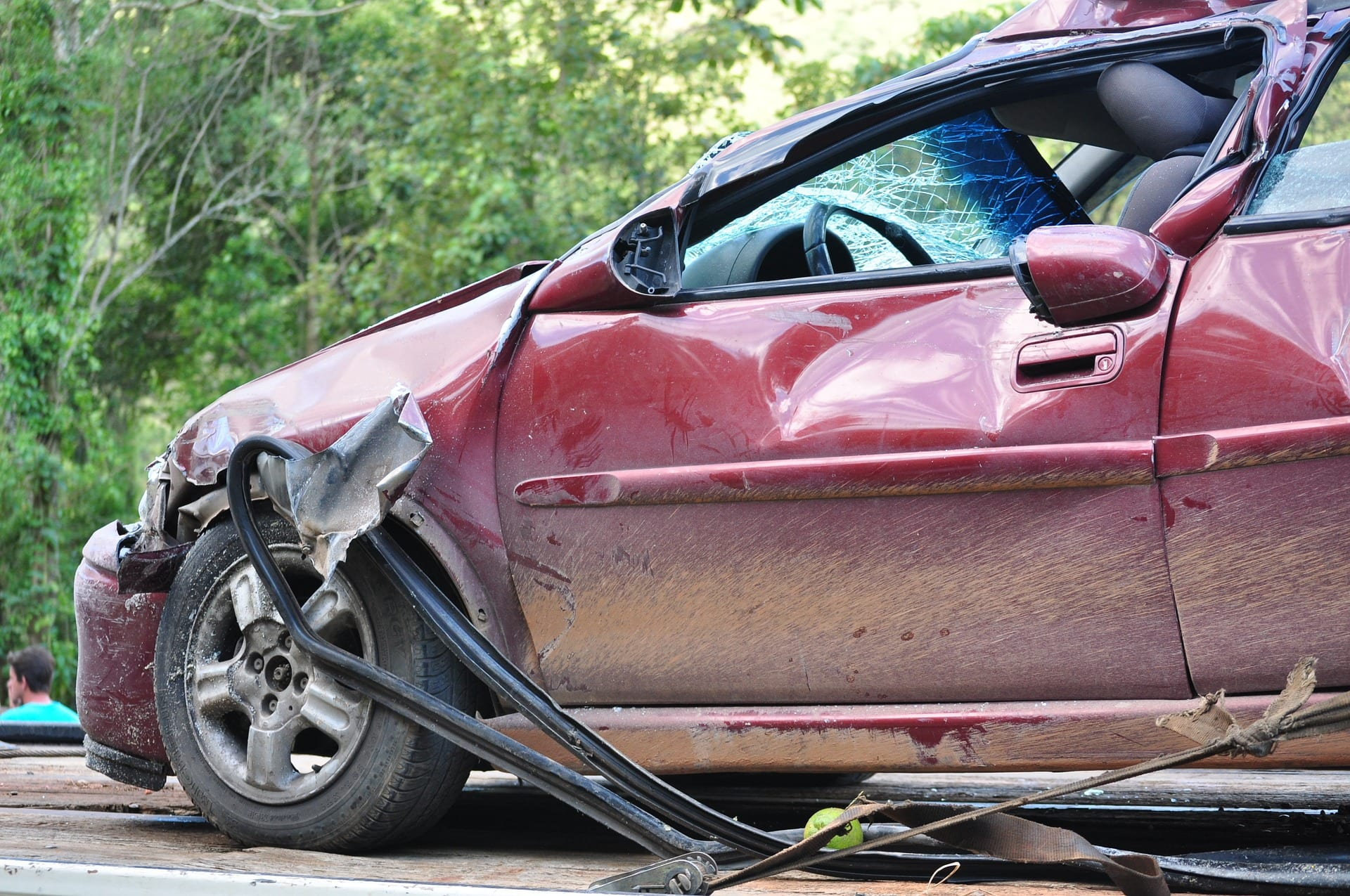 Maroon car badly damaged in auto accident; image by NettoFiguiredo, via Pixabay.com.