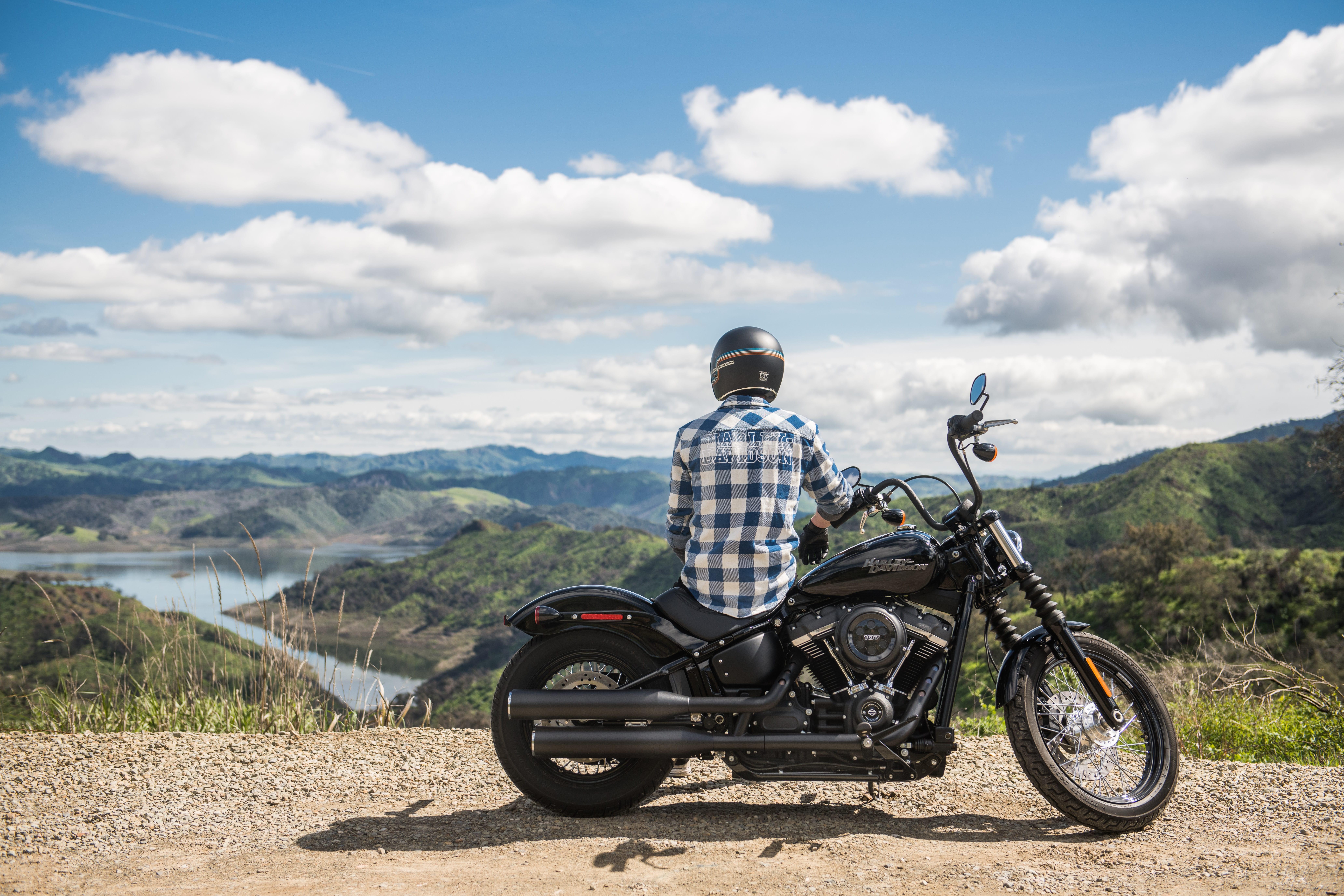 Man sitting on motorcycle, back to camera, looking at lake and mountains; image by Harley-Davidson via Unsplash.com.