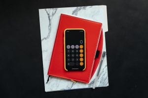 Black Android smartphone on red flip case; image by Kelly Skiiema, via Unsplash.com.