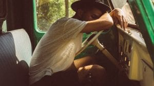 Man resting his arms and head on steering wheel of car; image by Lechon Kirb, via Unsplash.com.