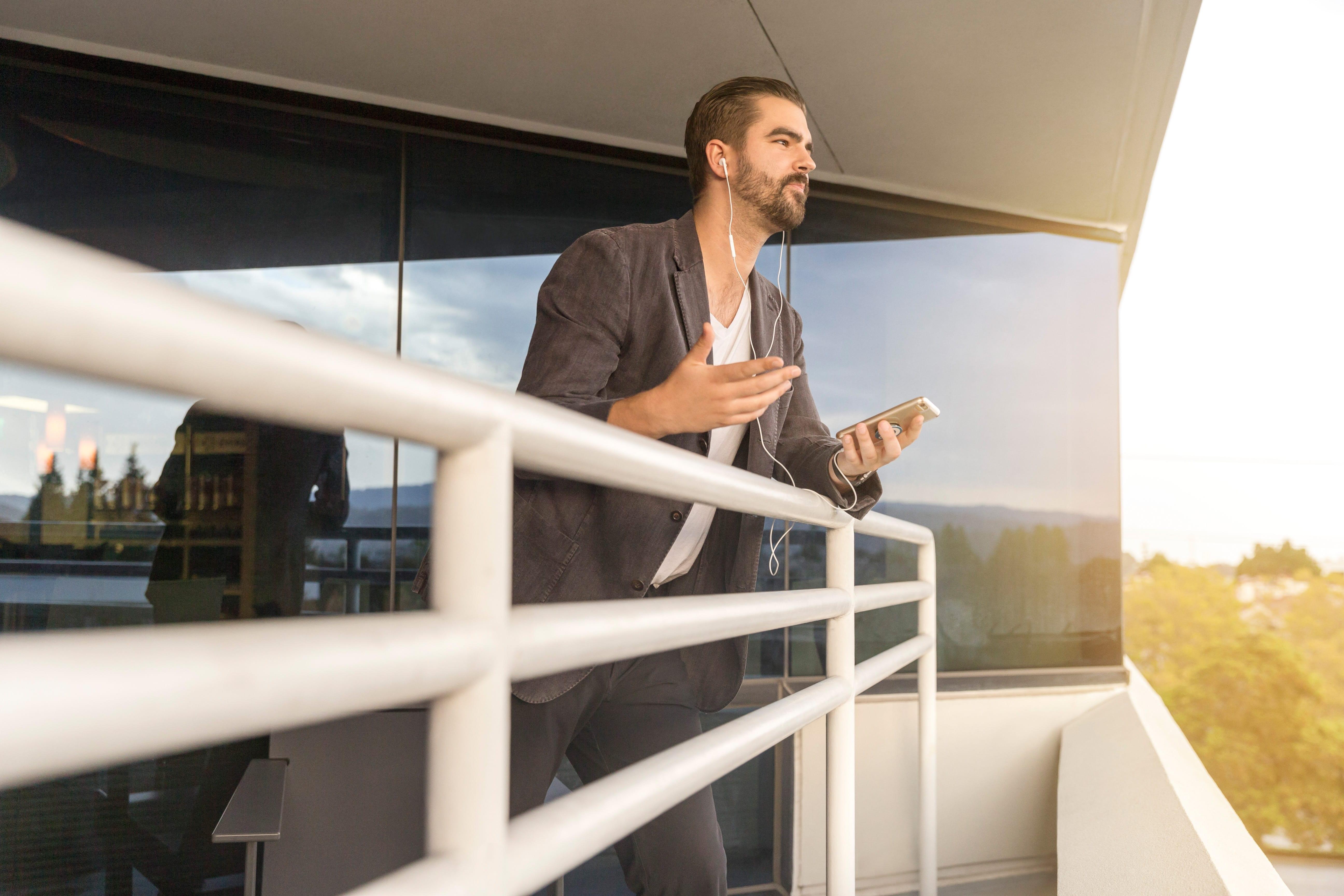 Man leaning on white metal rail; image by LinkedIn Sales Navigator, via Unsplash.com.