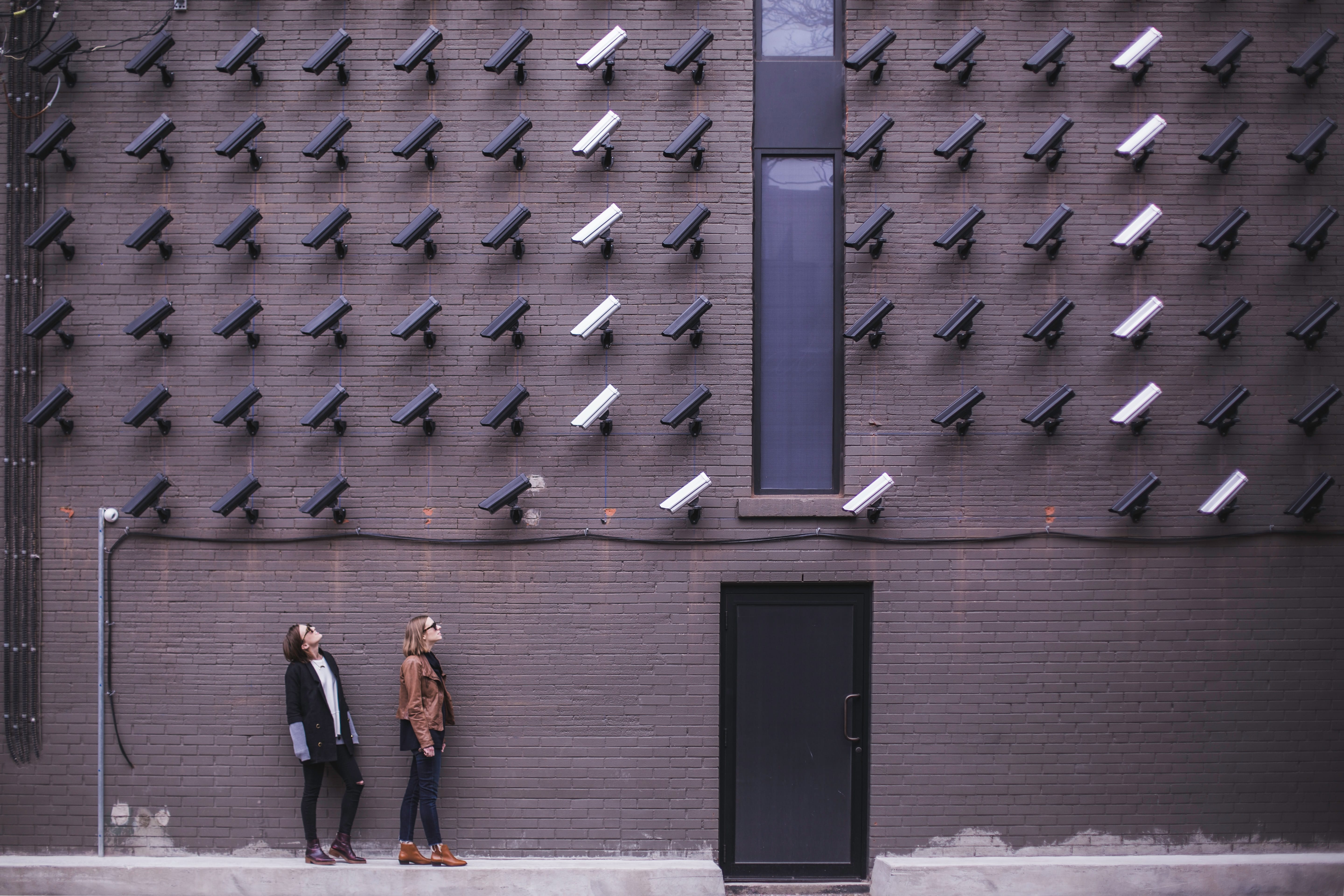 Two women facing security cameras mounted on structure above; image by Matthew Henry, via Unsplash.com.