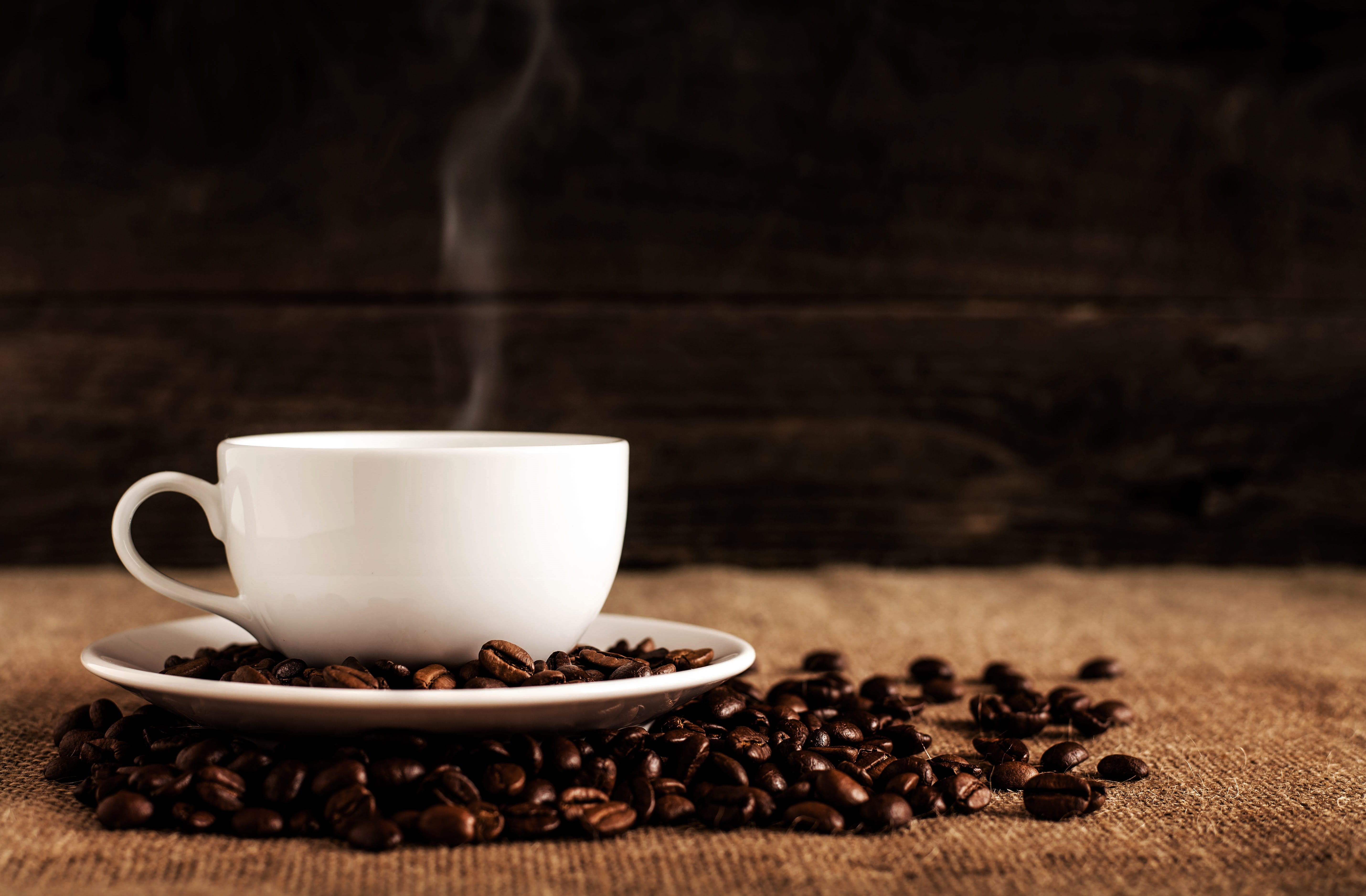 White ceramic mug and saucer with coffee beans on brown textile; image by Mike Kenneally, via Unsplash.com.