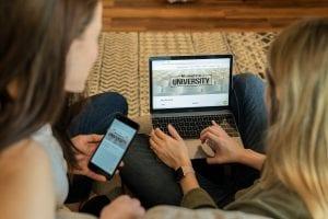 Woman using laptop sitting beside woman holding smartphone; image by Mometrix Test Prep, via Unsplash.com.